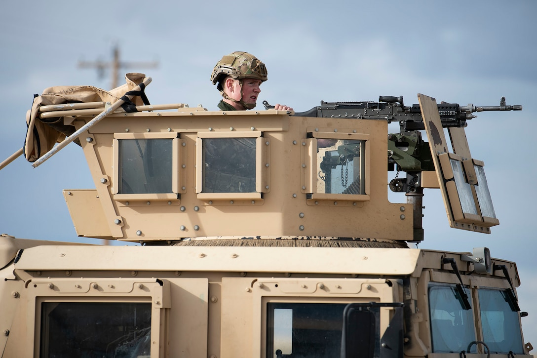 Defender sits in the turret of Humvee and looks towards the right side of the frame towards the distance.