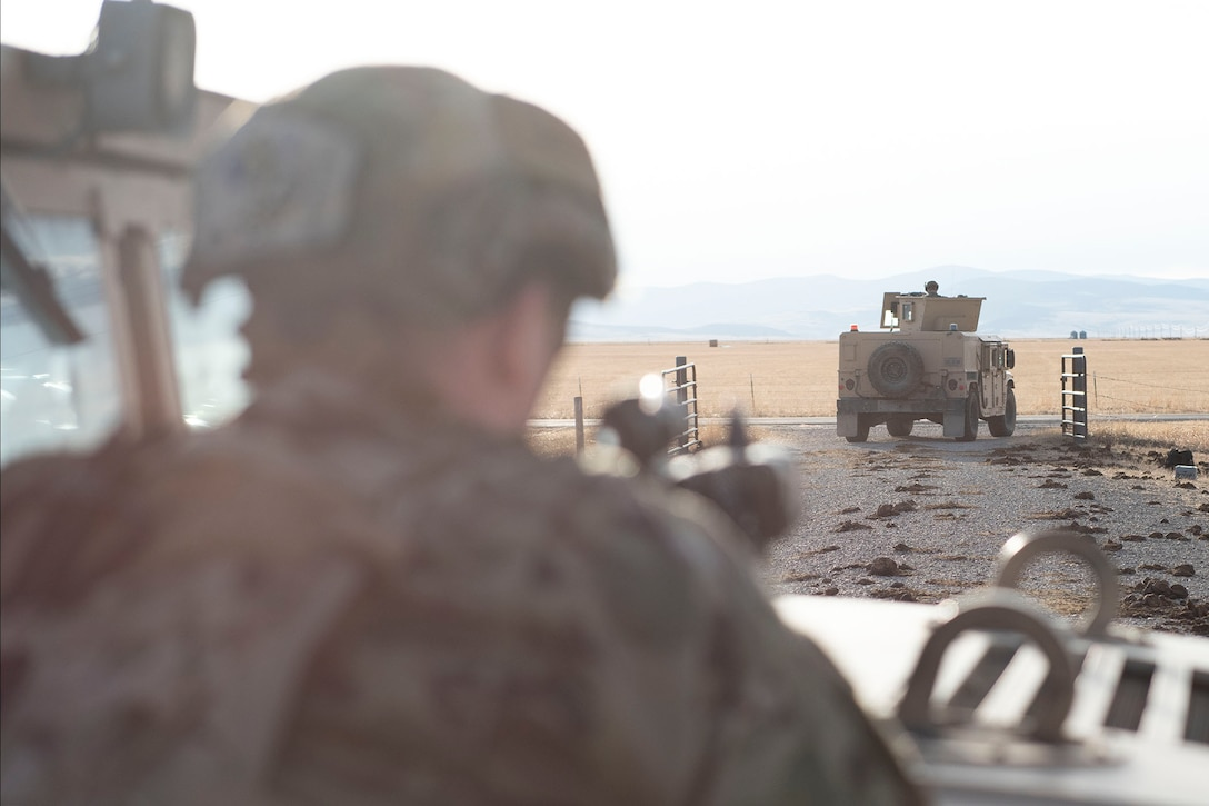 A defender leans against a humvee with his rifle pointing out in front of him (blurred) and in the forefront is a humvee driving off into the distance