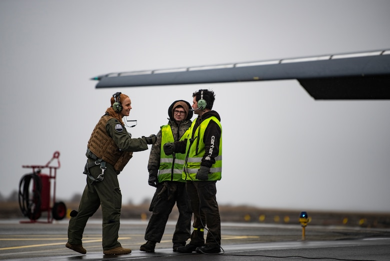 A pilot assigned to the 9th Expeditionary Bomb Squadron greets two crew chiefs at Ørland Air Force Station, Norway, March 23, 2021. Two B-1s participated in Amalgam Dart, a joint integration training mission consisting of a series of potential real-world scenarios designed to bolster U.S. aerospace warning and defense readiness. (U.S. Air Force photo by Airman 1st Class Colin Hollowell)