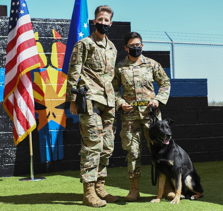 Maj. Kimberly Guest, left, 56th Security Forces Squadron commander, and Staff Sgt. Elizabeth Pedroza, 56th SFS military working dog handler, honor Boss, 56th SFS military working dog, as he retires March 19, 2021 at Luke Air Force Base, Arizona. Boss, who was recently diagnosed with cancer, served in the Air Force for seven years, completing two deployments to Al Dhafra Air Base, United Arab Emirates, and will live with Pedroza, his handler. As the Air Force prepares to retire a MWD, the dog's handler can request to adopt the dog enabling it to live the remainder of its life as a family member. Boss and Rango will retire and live at home with their respective handler. (U.S. Air Force photo by Staff Sgt. Amber Carter)