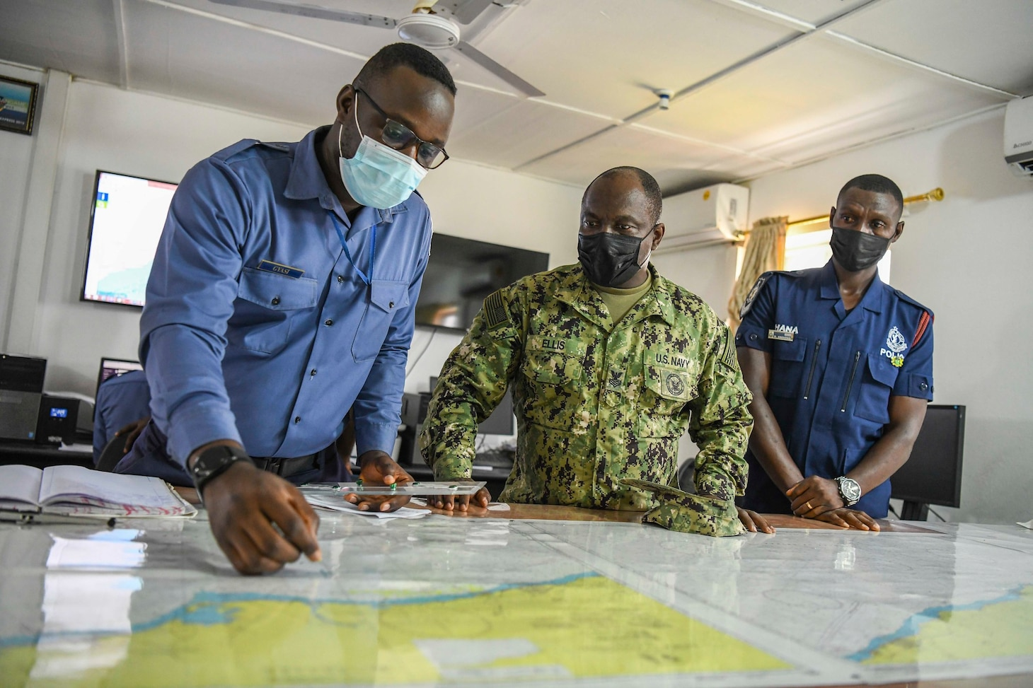Information Systems Technician 1st Class Samuel Ellis and Sailors in the Ghanaian Navy review a map in a maritime operation center during Exercise Obangame Express 2021, March 22, 2021.