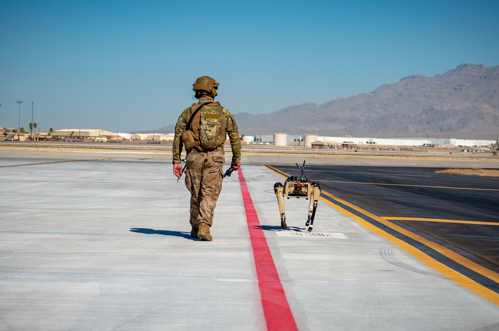 Airman with 321st Contingency Response Squadron security team patrols with Ghost Robotics Vision 60 prototype at simulated austere base during Advanced Battle Management System exercise on Nellis Air Force Base, Nevada, September 3, 2020 (U.S. Air Force/Zachary Rufus)