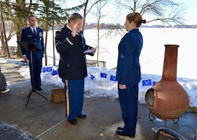 Man in uniform administers oath of office to female in uniform.