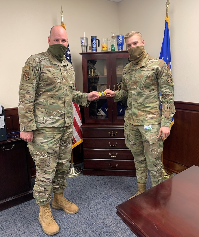 Command Chief hands Airman a coin.