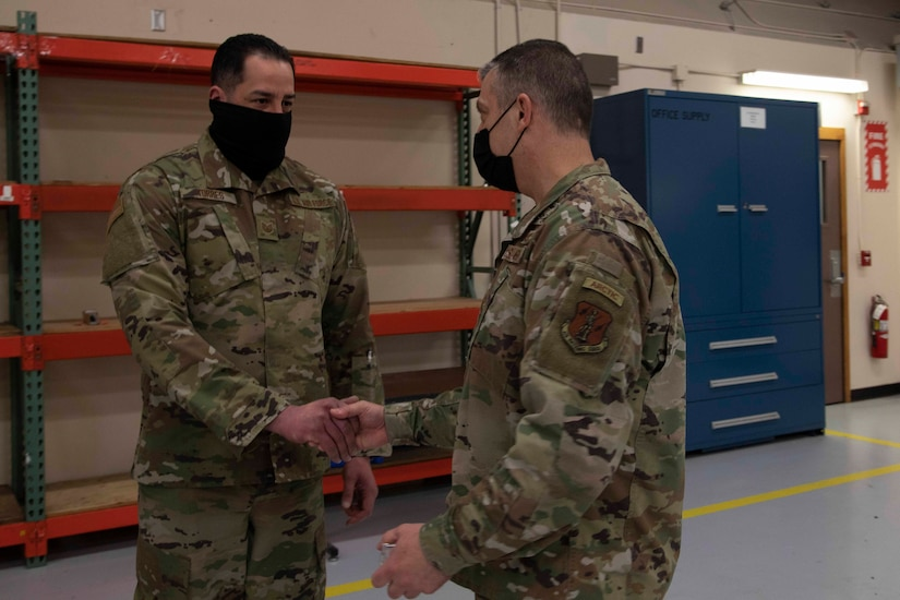 Maj. Gen. Torrence Saxe, adjutant general of the Alaska National Guard, right, awards Tech Sgt. Ernesto Torres a coin during a visit to Eielson Air Force Base, Alaska, March 23, 2021. (U.S. Army National Guard photo by Victoria Granado)