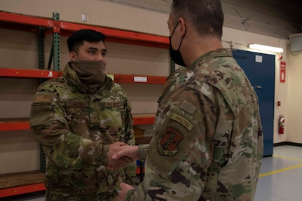 Maj. Gen. Torrence Saxe, adjutant general of the Alaska National Guard, right, awards Staff Sgt. Austin Cardines a coin during a visit to Eielson Air Force Base, Alaska, March 23, 2021. (U.S. Army National Guard photo by Victoria Granado)