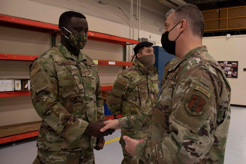 Maj. Gen. Torrence Saxe, adjutant general of the Alaska National Guard, right, awards Staff Sgt. Salem Dogbe a coin during a visit to Eielson Air Force Base, Alaska, March 23, 2021. (U.S. Army National Guard photo by Victoria Granado)