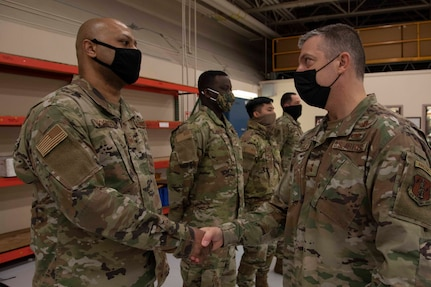Maj. Gen. Torrence Saxe, adjutant general of the Alaska National Guard, right, awards Tech Sgt. Steven Woodson a coin during a visit to Eielson Air Force Base, Alaska, March 23, 2021. (U.S. Army National Guard photo by Victoria Granado)