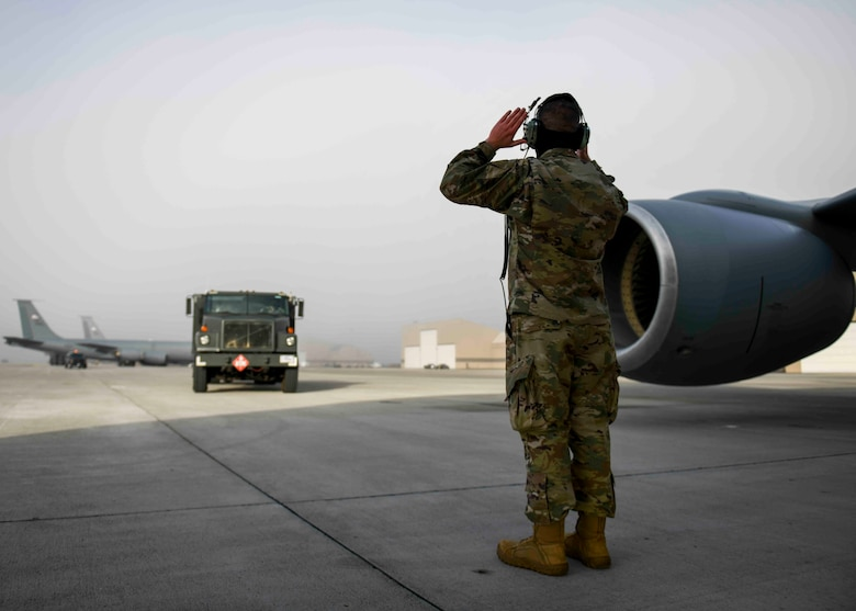 A 92nd Maintenance Squadron Airman guides a fuels truck toward a KC-135 Stratotanker in preparation for hot pit refueling on Fairchild Air Force Base, Washington, March 25, 2021. Being the first base in the Continental U.S. to bring the hot pit refueling capability CONUS, this showcases the innovation and preparedness Team Fairchild and the Air Mobility Command possess and implements. (U.S. Air Force photo by Airman 1st Class Kiaundra Miller)