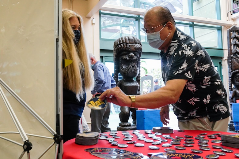 Yvonne Palmieri, Hickam Base Exchange store manager, assists Kenji Tanaka, retired U.S. Army veteran, during a pinning ceremony in honor of Vietnam War Veterans Day at Joint Base Pearl Harbor-Hickam, Hawaii, March 29, 2021. In 2017, President Donald Trump declared National Vietnam War Veterans Day because on this day in 1973 U.S. combat troops departed the Republic of Vietnam. (U.S. Air Force photo by Airman 1st Class Makensie Cooper)
