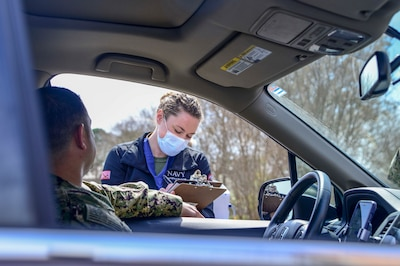 PORTSMOUTH, Va. (March 18, 2020) – Lt. j.g. Katherine Baile, an emergency nurse, conducts a practice screening at Naval Medical Center Portsmouth's (NMCP) COVID-19 drive thru screening and triage site outside of NMCP's Emergency Department (ED) on March 18.
