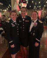Three female officers stand in dress uniform