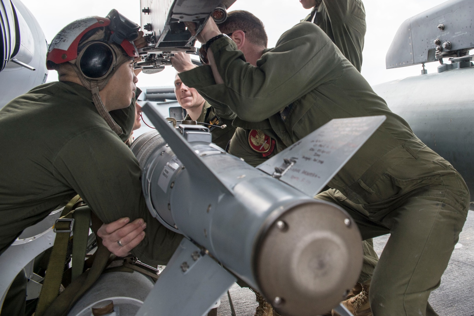 Marines attached to 26th Marine Expeditionary Unit load GBU-54 bomb onto AV-8B Harrier on flight deck of USS Kearsarge, supporting Operation Inherent Resolve, Arabian Gulf, December 28, 2015 (U.S. Navy/Tyler Preston)