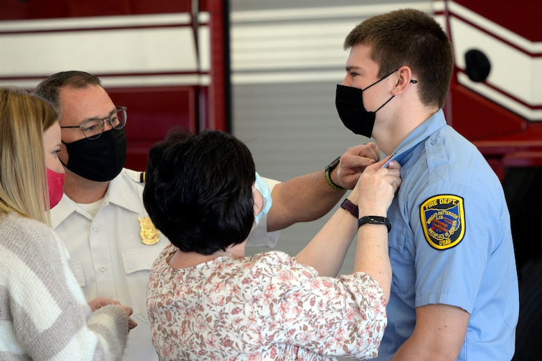 Ryan Hartman, a new Air Force firefighter with the 788th Civil Engineer Squadron, is pinned on by his mother, Vicki Hartman, and Fire Chief Jacob King during a promotion ceremony at Wright-Patterson Air Force Base, Ohio on Monday, March 29, 2021.