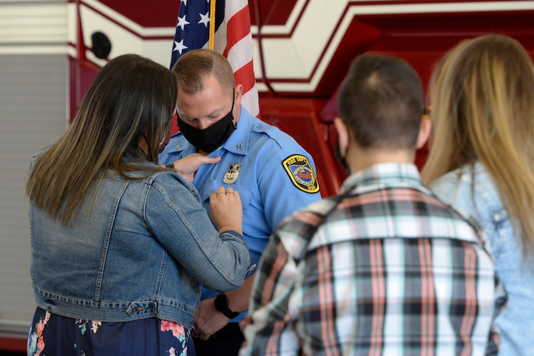 Air Force firefighter Capt. James Hammond with the 788th Civil Engineer Squadron, is pinned on by his wife, Ashlee, and children J.J. and Madison during a promotion ceremony at Wright-Patterson Air Force Base, Ohio on Monday, March 29, 2021.