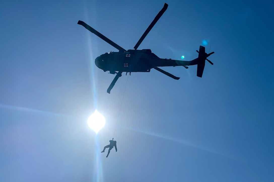 A soldier is hoisted toward an airborne helicopter.