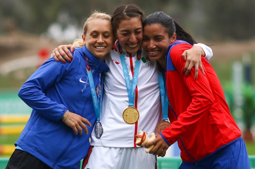Three women wearing sports uniforms and medals around their necks hug one another.