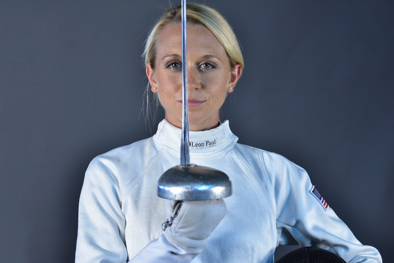 A woman holds a fencing sword.