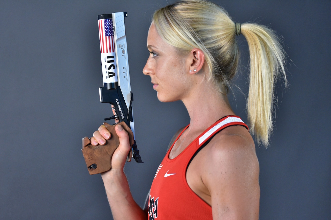A woman wearing a competition jersey holds a pistol used in competition.