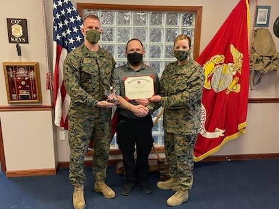 U.S. Marine Corps Col. Heather Cotoia, right, the commanding officer of the 4th Marine Corps District and Sergeant Major Kenneth L. Kuss, left, sergeant major of the 4th Marine Corps District award Daniel Feigley, center, the DHQ Civilian of the Year award at DLA New Cumberland, Pennsylvania, March 30, 2021. Feigley was awarded for his superior performance as the 4th Marine Corps District Telecommunications Manager.