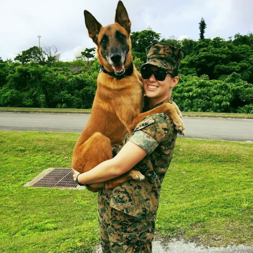 A Marine poses for a photo next to a dog.