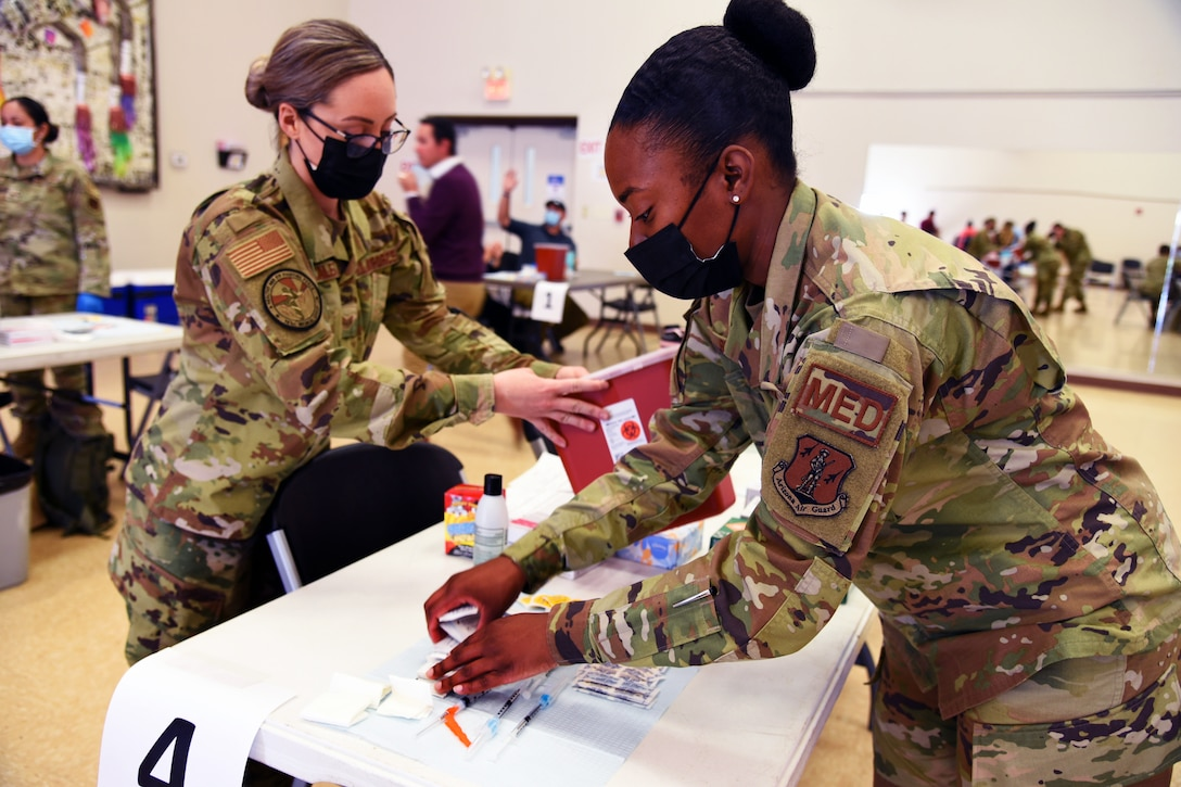 Two female service members wearing face masks help put medical supplies on a table.