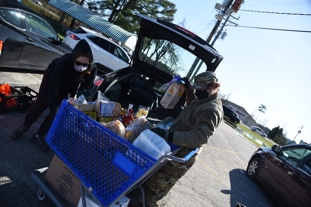 A soldier wearing a face mask and gloves helps a resident load groceries into her vehicle.