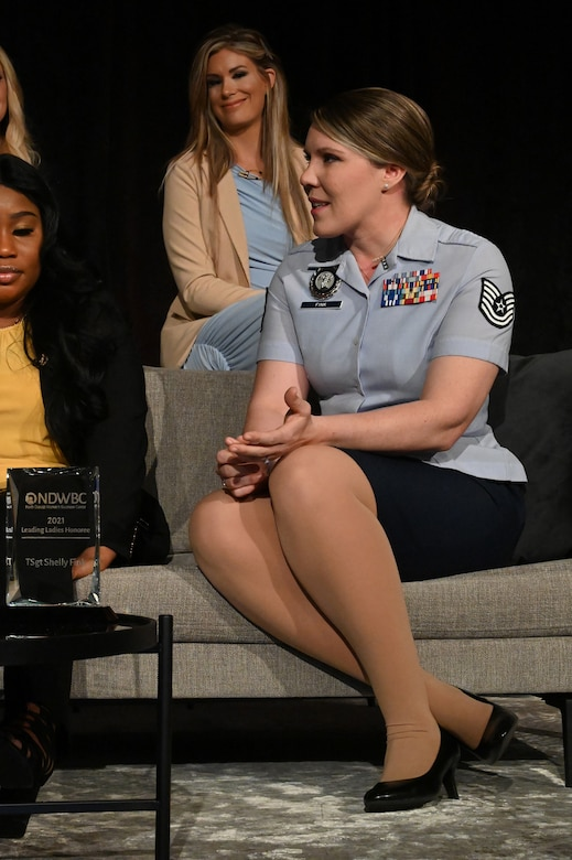 A female Airman in short-sleeve blue military uniform sits on a couch on a stage with three other women discussing women's issues in front of an audience at the Holiday Inn, Fargo, N.D., March 30, 2021.
