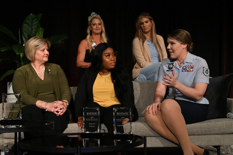 A female Airman in short-sleeve blue military uniform sits on a couch on a stage with four other women discussing women's issues in front of an audience at the Holiday Inn, Fargo, N.D., March 30, 2021.