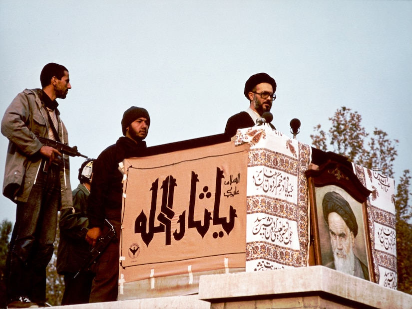 Muslim cleric, possibly Mohammad Mousavi Khoeiniha, speaking behind cloth-drapped stand displaying photograph of Ayatollah Khomeini, outside U.S. Embassy, Tehran, Iran, 1979 (Library of Congress/Sharok Hatami)