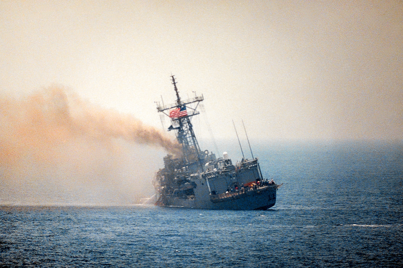 USS Stark listing to port after being struck by two Iraqi-launched Exocet missiles, Persian Gulf, May 17, 1987 (U.S. Navy)