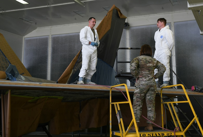 Chief Bass stands on a ladder talking to Airmen working on an F-22 Raptor.