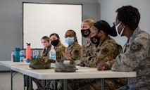 One female Airman in a line of six seated at a table is speaking.