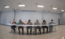Six female Airmen are sitting at a table and talk with each other.