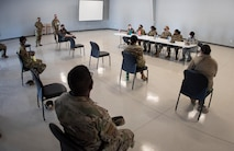 An audience is faced away from the camera and watching six female Airmen who are seated at a table.