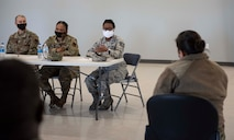 The back of a female Airmen facing three female Airmen sitting at a table. One at the table is talking.