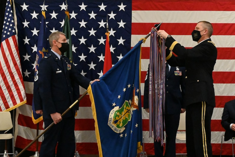 Maj. Gen. Al Dohrmann, the N.D. adjutant general places a symbolic streamer on the end of a flag staff being held by Col. Darrin Anderson, the 119th Wing commander during a ceremony on a stage in front of a large American flag at the North Dakota Air National Guard Base, Fargo, N.D., March 6, 2021.