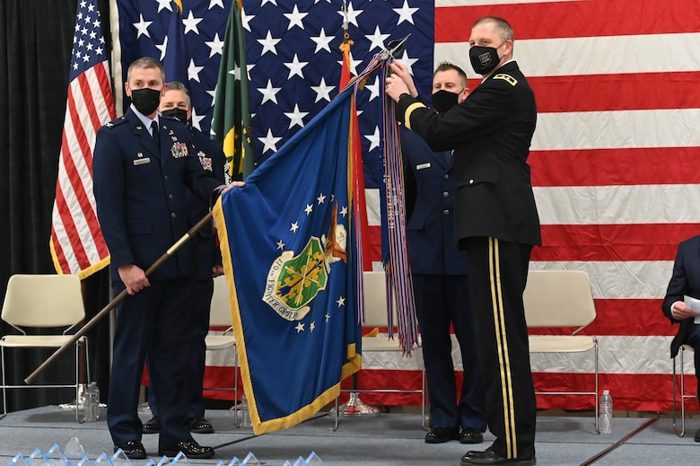 Four military members in uniform stand on a stage in front of a large American flag holding a flag staff to place a symbolic streamer representing the unit accomplishment of earning it's 22nd Air Force Outstanding Unit Award at the North Dakota Air National Guard Base, Fargo, N.D., March 6, 2021.