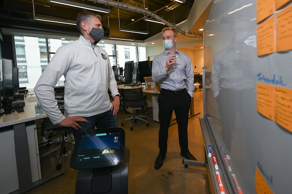 1st Lt. Ben Paulk, (right) a member of the Digital Phantom program and a program manager for AFNWC's Nuclear Command, Control and Communications Integration Directorate at Hanscom Air Force Base, Mass., speaks to Col. Tucker Hamilton, director of the Department of the Air Force-Massachusetts Institute of Technology Artificial Intelligence Accelerator, at its headquarters in Cambridge, Mass., March 26.