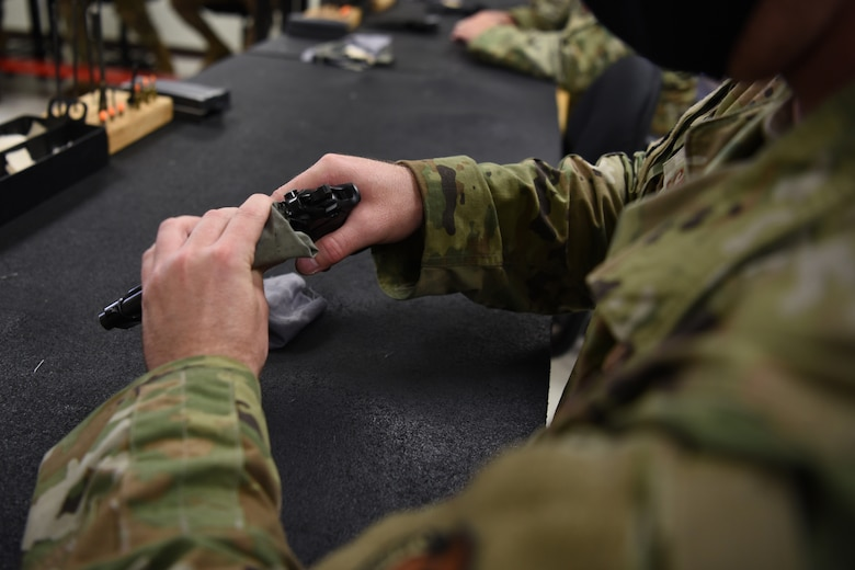 U.S. Air Force Tech. Sgt. Terry Snyder, 17th Communications Squadron radio frequency noncommissioned officer in charge, cleans a firearm during the Shooting in Excellence competition at the firing range, on Goodfellow Air Force Base, Texas, March 30, 2021. Snyder cleaned the firearm to remove any access carbon buildup that may have accumulated during its use, which protects the equipment from damage.  (U.S. Air Force Senior photo by Airman Abbey Rieves)
