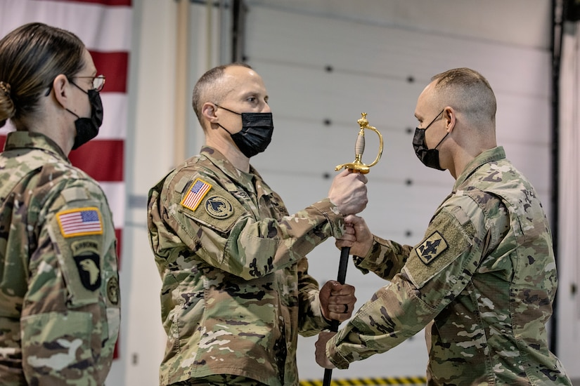 Col. Tim Brower (center), commander of 38th Troop Command, Alaska Army National Guard, passes the ceremonial scepter to Command Sgt. Maj. John Phlegar (right) during a change of responsibility ceremony on Joint Base Elmendorf-Richardson, Alaska, March 30. Phlegar assumed the role as the senior enlisted leader from Command Sgt. Maj. Maureen Meehan (left), making Phlegar the senior noncommissioned officer in charge of the brigade. (U.S. Army National Guard photo by Edward Eagerton)