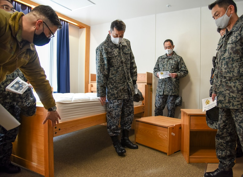 U.S. Air Force Master Sgt. William Castro, 35th Civil Engineer Squadron Unaccompanied Housing superintendent, explains the purpose of the furniture layout to Japan Air Self-Defense Force 3rd Air Wing leaders during a tour of the unaccompanied housing dormitory campus at Misawa Air Base, Japan, Feb. 26, 2021. As they are in the process of upgrading their unaccompanied housing living quarters, the JASDF leaders took the tour to gain some perspective on how the 35th Fighter Wing manages its dormitory campus. (U.S. Air Force photo by Tech. Sgt. Timothy Moore)