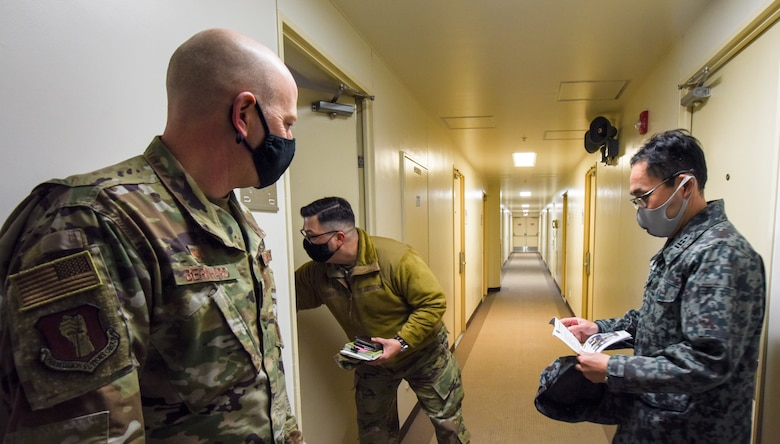 U.S. Air Force Master Sgt. William Castro, 35th Civil Engineer Squadron Unaccompanied Housing superintendent, opens a door to a dormitory room for Col. William Bernhard, 35th Mission Support Group commander, and Japan Air Self-Defense Force Col. Kato Fumihiko, 3rd Air Wing vice commander, during a tour of the unaccompanied housing dormitory campus at Misawa Air Base, Japan, Feb. 26, 2021. Bernhard hosted Fumihiko and other JASDF leaders on the tour as they learned about the 35th Fighter Wing's quality of life standards, room layouts, and other management techniques used to provide a quality living standard for unaccompanied Airmen. (U.S. Air Force photo by Tech. Sgt. Timothy Moore)
