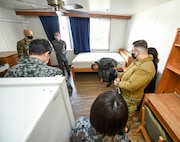 U.S. and Japanese Airmen stand in a dormitory room on the 35th Fighter Wing's Unaccompanied Housing campus at Misawa Air Base, Japan, Feb. 26, 2021. As they are in the process of improving their own campus, Japan Air Self-Defense Force leaders from the 3rd Air Wing took the tour to gain some perspective on how the 35th FW manages and operates its campus. During the tour, they got to ask questions about the furniture and appliance costs, determining the occupants of rooms, shared living spaces and even mold prevention. (U.S. Air Force photo by Tech. Sgt. Timothy Moore)