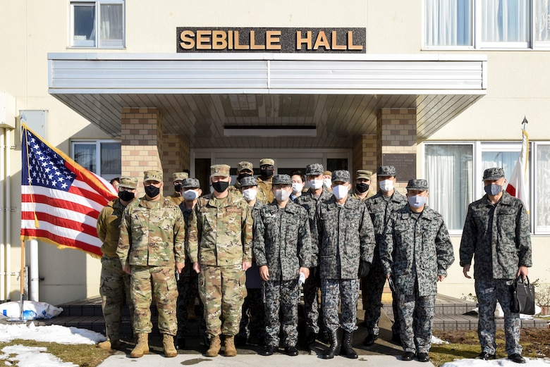 U.S. and Japanese Airmen pose for a group photo after touring the 35th Fighter Wing's unaccompanied housing campus at Misawa Air Base, Japan, Feb. 26, 2021. U.S. Air Force Col. William Bernhard, 35th Mission Support Group commander, hosted Japan Air Self-Defense Force Col. Kato Fumihiko, 3rd Air Wing vice commander, and other JASDF leaders on the tour as they learned about the 35th FW's quality of life standards, room layouts, and other management techniques used to provide a quality living standard for unaccompanied Airmen. (U.S. Air Force photo by Tech. Sgt. Timothy Moore)