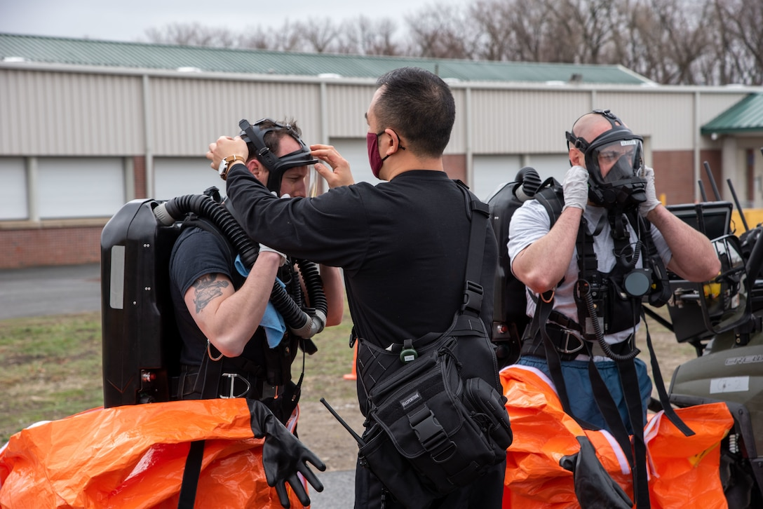 Sgt. Dan Pyo of the 14th Civil Support Team assists teammate Sgt. Justin Madore during a training exercise at the Eastern States Exposition Center in West Springfield, Mass., on March 25, 2021. The Training Proficiency Evaluation is led by U.S. Army North for a CST to validate their training and equipment every 18 months.