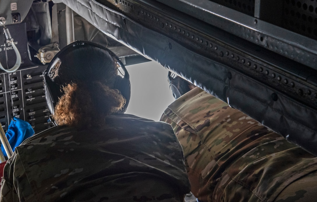 U.S. Air Force Chief Master Sgt. Shae Gee, 6th Air Refueling Wing command chief looks on as Airman Keegan Salas, a 50th Air Refueling Squadron boom operator, operates the controls on the boom of a KC-135 Stratotanker aircraft, March 30, 2021.
