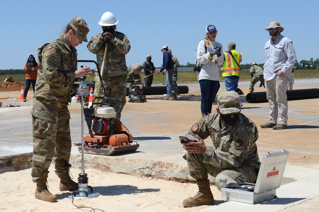 U.S. Air Force Master Sgt. Elizabeth Sailer (left), 169th Civil Engineer Squadron, works with fellow engineers Senior Master Sgt. Matthew Novak, HQ Pacific Air Forces, Joint Base Hickam, Hawaii, and Tech. Sgt. Adam Ballash, 36th Civil Engineer Squadron, Anderson Air Force Base, Guam, to perform a soil test using a Clegg hammer during an Expedient and Expeditionary Airfield Damage Repair (E-ADR) Joint Capability Technology Demonstration at McEntire Joint National Guard Base, South Carolina, April 22, 2021. The demonstration simulates the rapid repair of a battle damaged runway. (U.S. Air National Guard photo by Lt. Col. Jim St.Clair, 169th Fighter Wing Public Affairs)