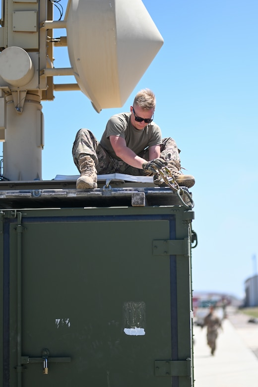 Senior Airman Brendan Hoffman, 727th Special Operations Aircraft Maintenance Squadron ground control station technician, secures a satellite on a shipping container, April 20, 2021, on Point Mugu Naval Air Station, California. Airmen and Guardians from the 49th Wing, Holloman Air Force Base, New Mexico; 452nd Air Mobility Wing, March Air Reserve Base, California; 27th Special Operations Wing, Cannon Air Force Base, New Mexico, and the 432nd Air Expeditionary Wing, Creech AFB, Nevada, joined to execute Exercise Agile Reaper. (U.S. Air Force photo by Senior Airman Kristin Weathersby)
