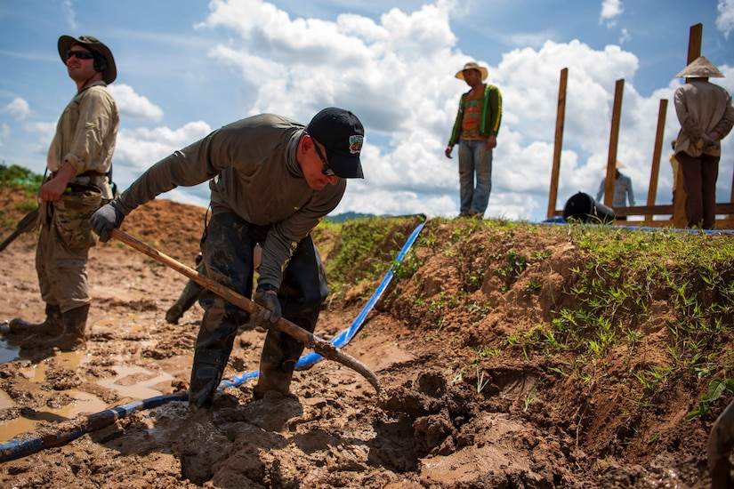 A man uses a shovel to dig in the ground.